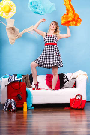 Cleaning in the closet, fashion, happiness concept. Woman standing on sofa throwing up lot of clothes. Clothing flying all over the place