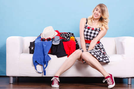 Packing problems, necessary things during the trip concept. Happy woman sitting on sofa, getting ready for vacation, choosing clothes to pack into suitcase Stock Photo