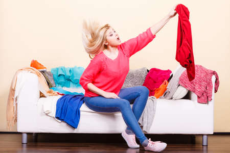 Style dilemmas concept. Shocked woman does not know what to wear sitting on messy couch with piles of clothes and looking through clothing.