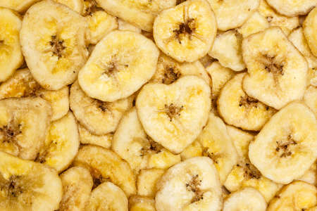 Banana chips, dehydrated slices of fresh ripe bananas as food background.