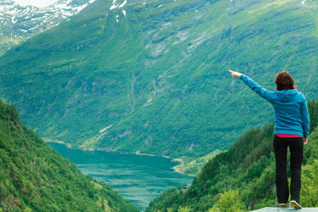 Travel concept. Tourist woman looking and pointing with finger at fjords beautiful mountains landscape in Norway Stock Photo