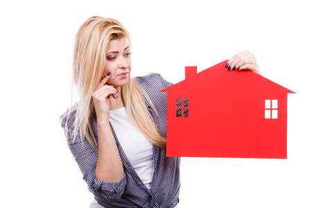 Ownership property real estate concept. Thinking blonde girl holding red paper house symbol. New flat apartment. Isolated on white