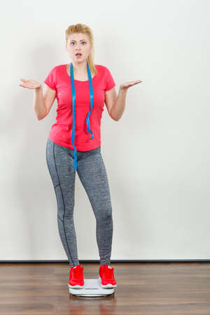 Healthy fit life style, controling body concept. Worried woman wearing sportswear, leggings and trainers standing on weight machine holding measuring tape.
