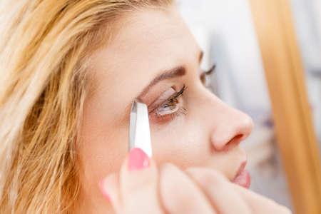 plucking: Woman plucking eyebrows depilating with tweezers closeup part of face. Girl tweezing removing her facial hairs..