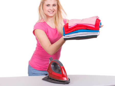 Household duties, perfect housewife concept. Woman holding pile of folded clothes after laundry and ironing