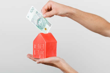Household savings and finances, economy concept. Man putting zlotych money into a piggy bank in the shape of a house, studio shot on grey background Stock Photo
