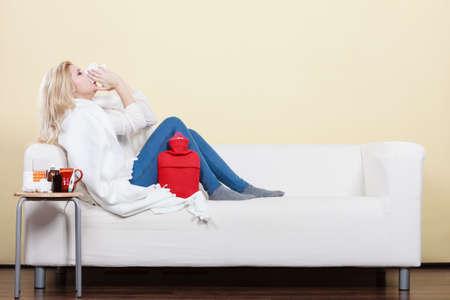 Sickness, seasonal virus problem concept. Woman being sick having flu lying on sofa sneezing into tissue