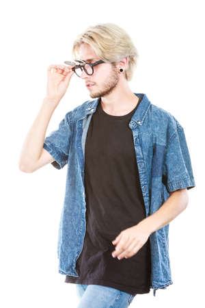 Men fashion, modeling concept. Hipster man looking for something wearing jeans outfit and eccentric glasses studio shot, isolated