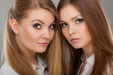 Family relationships, friendship concept. Two beautiful women sisters, blonde and brunette with windblown hair posing charmingly. Stock Photo