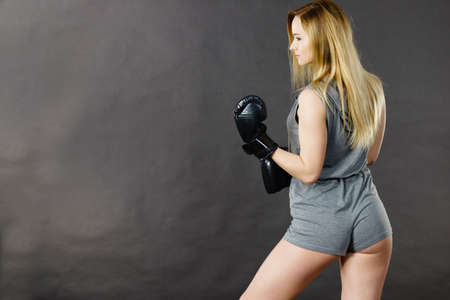 Sportsmanship fairplay and strong body. Young woman fighting boxing. Blonde girl wearing black punch gloves. Sport and fitness, power, exercising, side view on gray Stock Photo