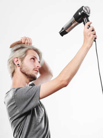 Hairstyle and fashion. Young trendy male hairstylist barber with new idea of look changing. Blonde man holding hair dryer and comb creating new hairdo