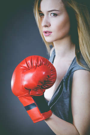 Young sensual woman, blonde attractive girl wearing red punch boxing gloves. Sport fitness and power concept.