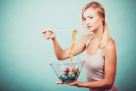 Diet, healthy food, weight loss and slim body concept. Fit fitness girl holding bowl eating colorful measuring tapes Stock Photo