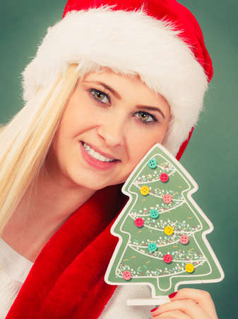 Enjoying cozy holiday interior, seasonal accessories concept. Blonde young woman in Santa hat holding little decorative plastic Christmas tree. Stock Photo