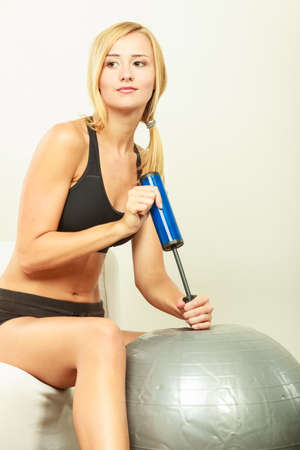 fitball: Sport, training, gym and lifestyle concept. Young attractive slim woman in sportswear with air pump inflating fit ball, fitness exercise