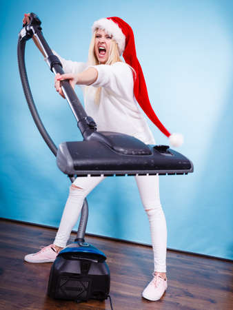 Woman vacuuming the house, last minute. Teen girl in santa helper hat with vacuum cleaner, angry furious face expression. Christmas time and housework concept. Stock Photo