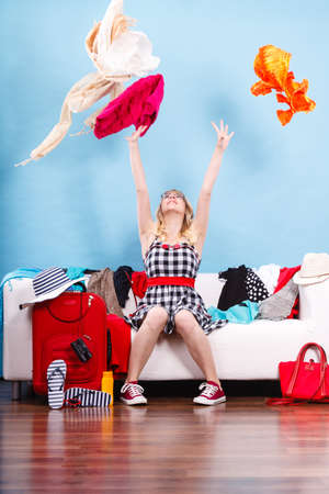 Cleaning in the closet, packing for travel, fashion, happiness concept. Woman sitting on sofa throwing up lot of clothes. Clothing flying all over the place Stock Photo