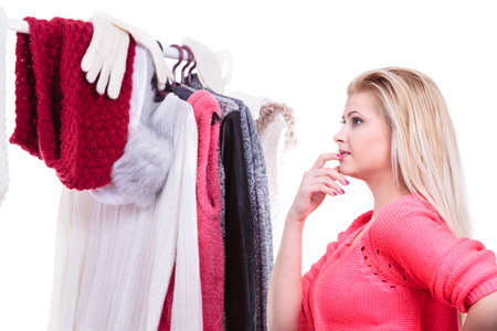 Young woman indecision in wardrobe, teen blonde girl choosing her warm winter fashion outfit in walk in organized closet. Shopping store clothing rack.