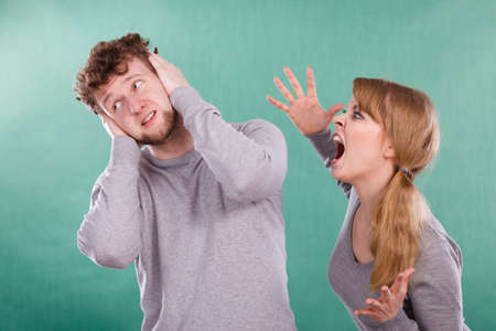 Violence against man. Aggressive woman yelling shouting on scared afraid man. Negative relations in partnership. Expressive young lady screaming.
