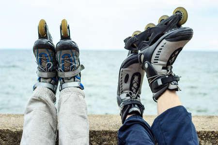 Primer plano de la gente amiga de patines. La mujer y el hombre que se relaja al aire libre.