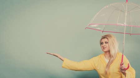 Blonde woman wearing yellow raincoat holding transparent umbrella checking weather if it is raining. Stock fotó - 88764938