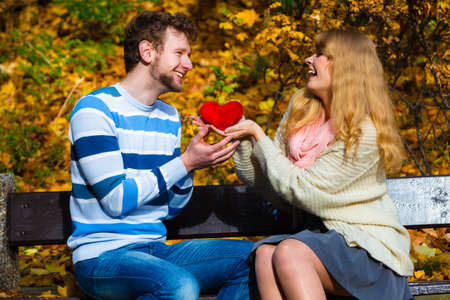 Expressing feelings and affection. Confess love with romantic gesture. Young couple sit on bench in park holding plush heart smiling and sharing good emotions. Stock Photo
