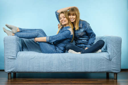 Friendship, human relations concept. Two happy women friends or sisters wearing jeans shirts sitting on sofa having fun.