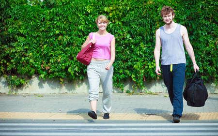 Pareja feliz hombre y mujer con gimnasia de deporte bolsas cruzando peatones paso de peatones al aire libre. Chica joven activo y el individuo en traje de entrenamiento de ropa deportiva. Felicidad.