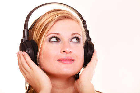 Portrait, musicaly, passion concept. Studio shot blonde young woman listening to music on big headphones, looking up and thinking, isolated,