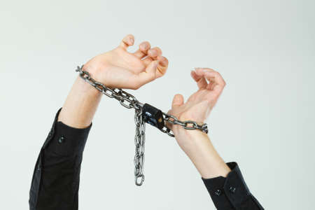 No freedom, social problems, human rights concept. Man with chained hands, studio shot on light grey background Stock fotó