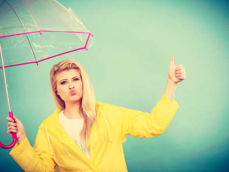Blonde woman wearing yellow raincoat holding transparent umbrella checking weather if it is raining showing thumb up gesture Stock fotó
