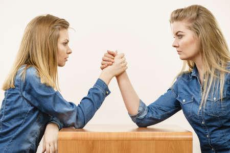 Dos mujeres compasivas serios que tienen lucha de lucha del brazo, compiten con uno a.