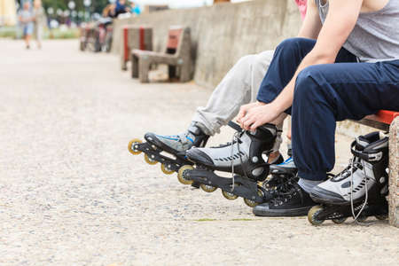 Closeup of people friends putting on roller skates outdoor. Woman and man sitting on bench. Stock Photo