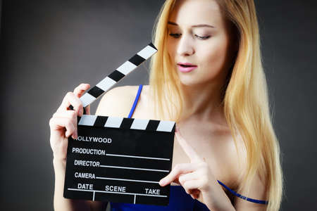 Woman holding professional film slate, movie clapper board. Hollywood production objects concept. Studio shot on black background. Stock Photo