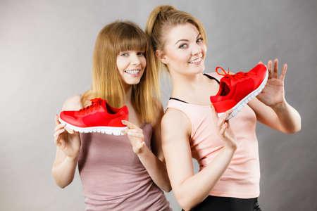 Dos mujeres sonrientes deportivas felices que presentan los zapatos rojos de los amaestradores de la ropa de deportes, calzado cómodo perfecto para el entrenamiento y el entrenamiento. Foto de archivo - 89716951