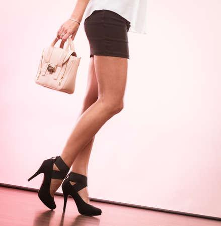 Elegant outfit. Female fashion. Girl fashionable clothes high heels shoes short skirt holding bag handbag.