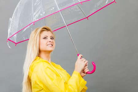 Good mood during rainy day. Happy blonde woman wearing yellow raincoat holding transparent umbrella