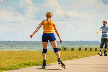 Active lifestyle people and freedom concept. Young fit couple on roller skates riding outdoors on sea coast, woman and man rollerblading enjoying time together