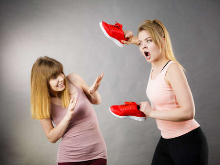 Agressive women having argue fight using shoes, female friend being scared. Violance concept. Stock Photo