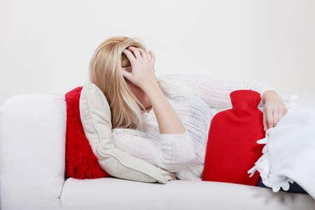 Los períodos menstruales dolorosos y problemas menstruales concepto calambre. Mujer que tiene calambres en el estómago se extiende sobre cofa sentirse muy mal la botella de agua caliente a sentir un poco de alivio