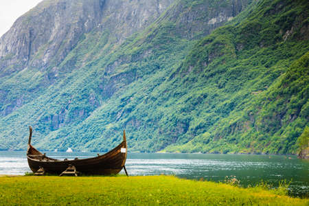 Old wooden viking boat on seashore in norwegian nature. Mountains and fjord Sognefjord. Tourism and traveling concept Stock Photo