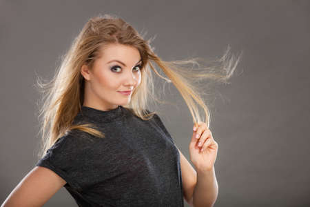 Haircare, beauty, hairstyling concept. Portrait of young attractive blonde woman wearing dark t shirt having windblown beautiful long hair.