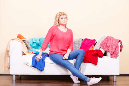Clothing dilemmas concept. Woman does not know what to wear sitting on messy couch with piles of clothes. Stock Photo