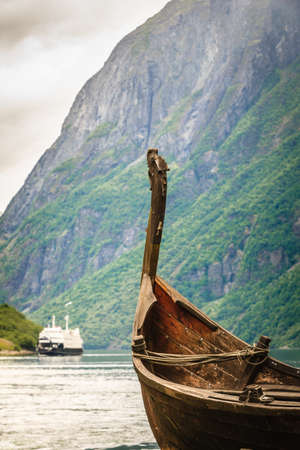 Old wooden viking boat on seashore in norwegian nature and ferryboat on water fjord. Mountains and Sognefjord. Tourism and traveling concept