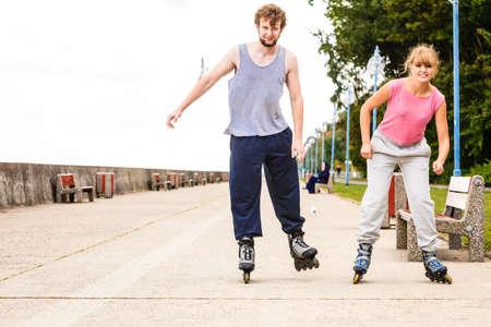 Active jóvenes amigos en traje de entrenamiento patinaje al aire libre. Mujer feliz y montar hombre que goza el deporte.