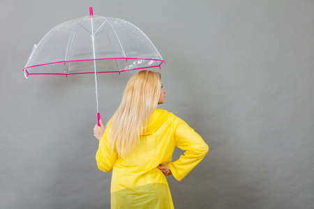 Blonde woman wearing yellow raincoat holding transparent umbrella checking weather if it is raining. Back view.