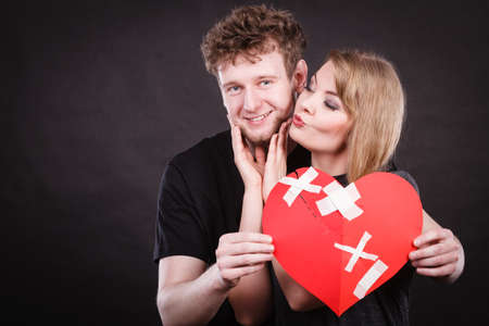 Heal love concept. Couple woman and man holding two halves of broken heart fixed with plaster bandage going to be joined in one.  Stock Photo