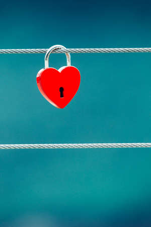 Tourism vacation and travel. Red love heart shaped lock padlock on bridge outdoor, blurred background Reklamní fotografie