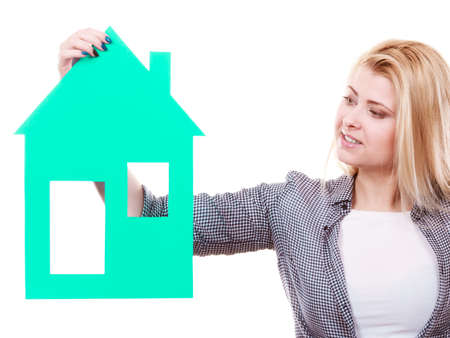 Dream about stabilization and family. Blonde girl holding green paper house model cutout. New flat apartment. Isolated on white Stock Photo