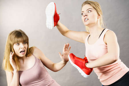 Agressive women having argue fight using shoes, female friend being scared. Violance concept. 스톡 콘텐츠